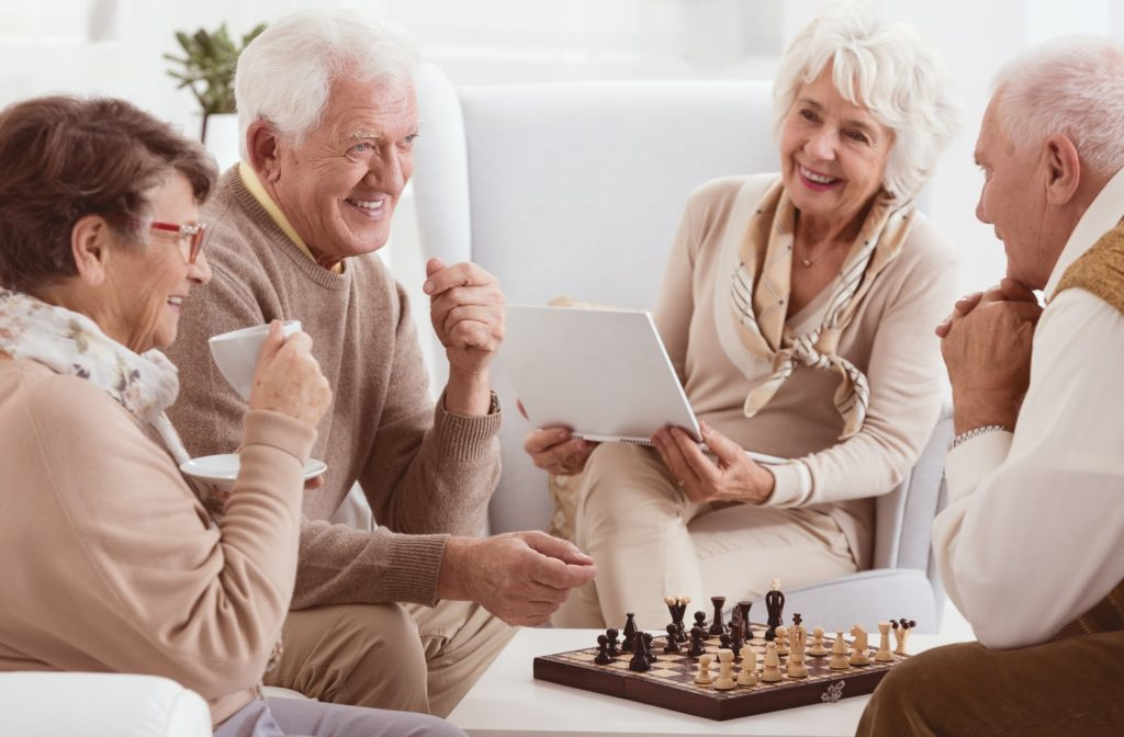 Happy seniors socializing and playing chess at senior home community.